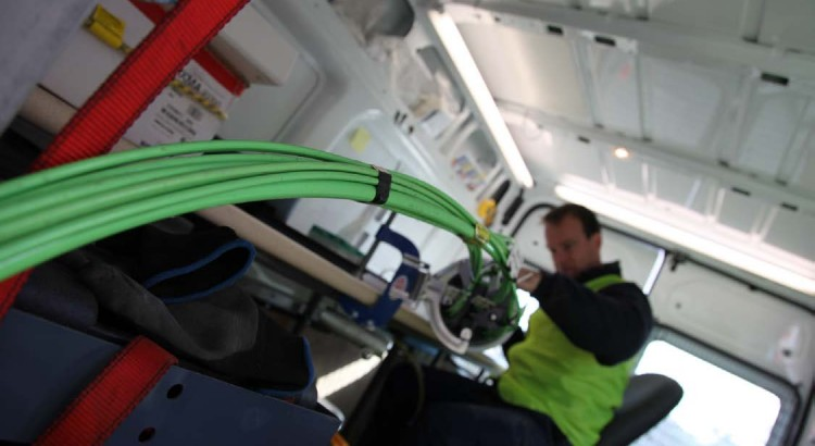 NBN technician splicing fibre in a van